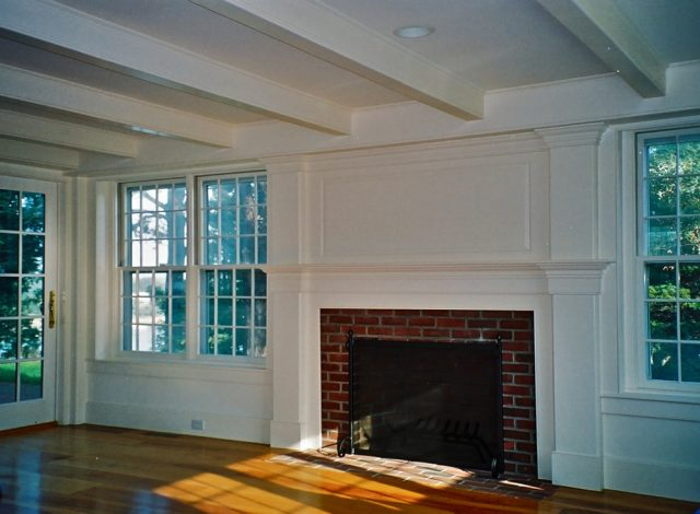 Paneled fireplace and mantel and ceiling beams at living room of Cape Cod custom home