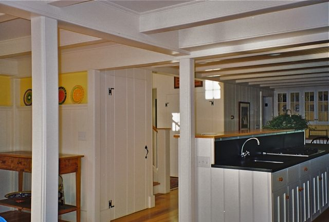 Beamed ceiling and column at open plan kitchen and living area in Orleans, MA Cape Cod house
